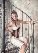 Beautiful steampunk woman on the stairway — Stock Photo