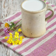 Fresh milk in ceramic mug and flowers — Stock Photo