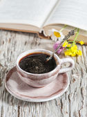 Cup of coffee and flowers in open book — 图库照片