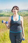 Beautiful plus size woman exercising with dumbbells — Stockfoto