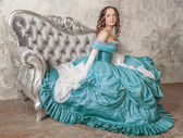 Beautiful woman in medieval dress on the sofa — Foto de Stock