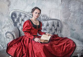 Beautiful woman in medieval dress on the sofa with book — Stock Photo