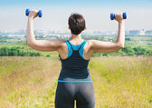 Plus size woman exercising with dumbbells — Stock Photo