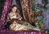 Beautiful woman in medieval dress reading book — Stock Photo