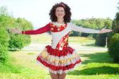 Young woman in irish dance dress welcoming outdoor — Stock Photo