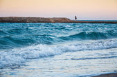 Sea coast in the evening and lonely figure of a man in the dista — Stock Photo