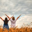 Couple staying with raised hands at a wheat field — Stock Photo #19782583