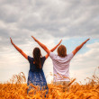 Couple staying with raised hands at a wheat field — Stock Photo #19782605