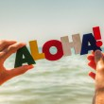 Female's hand holding colorful word 'Aloha' — Stock Photo