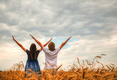 Couple staying with raised hands at a wheat field — Stock Photo