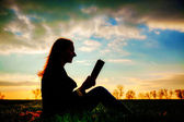 Teen girl reading book outdoors — Stock Photo
