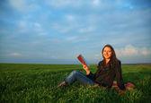 Teen girl reading the Bible outdoors — Stock Photo
