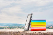 Stack of colorful books with electronic book reader — Stock Photo