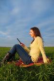 Teen girl reading electronic book outdoors — Stock Photo