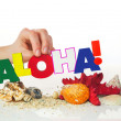 Foto de Stock  : Female's hand holding colorful word 'Aloha'