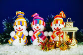 Three snowman with a lantern — Stockfoto