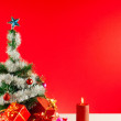 Christmas gifts with candles over red background — Stockfoto #7977002