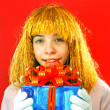 Teen girl with a present against red background — Stock Photo #8409306