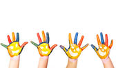 Kids hands in colorful paint with smiles — Stock Photo