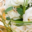 Bouquet of white roses with closeup of golden wedding rings on white rose — Stock Photo