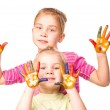 Two happy girls showing hands painted in bright colors — Stock Photo #19298353
