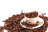 Kávová zrna a šálek kávy pozadí — Stock fotografie