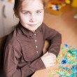 Stock Photo: Cute little girl solving puzzles
