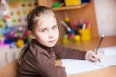 Cute little girl writing her homework — Stock Photo