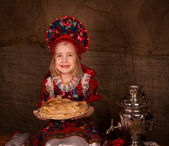 Beautiful russian girl with full plate of pancakes — Stock Photo