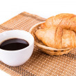 Постер, плакат: Fresh and tasty French croissants in a basket and cup of coffee served