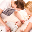 Young happy family: mother, father and baby lying — Stock Photo