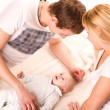 Young happy family: mother, father and baby lying — Stock Photo #22764822