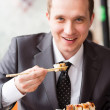 Young handsome businessman eating sushi with sticks — Stock Photo