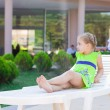 Beautiful little girl resting on a lounge at the hotel swimming pool  — Stock Photo