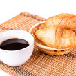 Fresh and tasty French croissants in a basket and cup of coffee served — Foto Stock