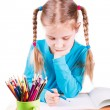 Adorable little smiling girl drawing picture in sketchbook with colored pencils — Stok Fotoğraf #23426124