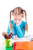 Adorable little smiling girl drawing a picture in a sketchbook with colored pencils — Stock Photo