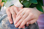 Hands of bride and groom and rings with wedding bouquet — Stock Photo