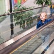 Stock Photo: Cute little child in shopping center standing on moving escalator