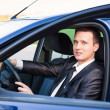 Handsome young businessman in his new car — Stock Photo