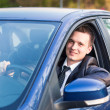 Handsome young businessman in his new car - Stock Photo