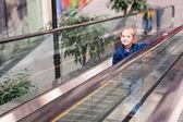 Lindo niño pequeño en el centro comercial que está parado en las escaleras mecánicas en movimiento — Foto de Stock
