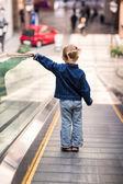Bambino carino in centro commerciale in piedi sulla scala mobile in movimento — Foto Stock