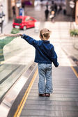 Cute little child in shopping center standing on moving escalator — Zdjęcie stockowe