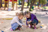 Happy little girls playing in a sendbox — Stock Photo