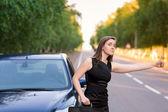 Bella empresaria cerca de su coche tratando de detener otro coche — Foto de Stock