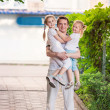 Happy young father holding his kids outdoor — Stock Photo #26007009