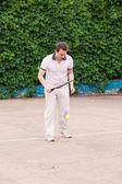 Ekspresyjny młody człowiek, grać w tenisa — Zdjęcie stockowe