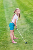 Cute little girl playing golf on a field — Stock Photo