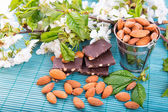 Almonds in a backet with pieces of chocolate with nuts — Stock Photo